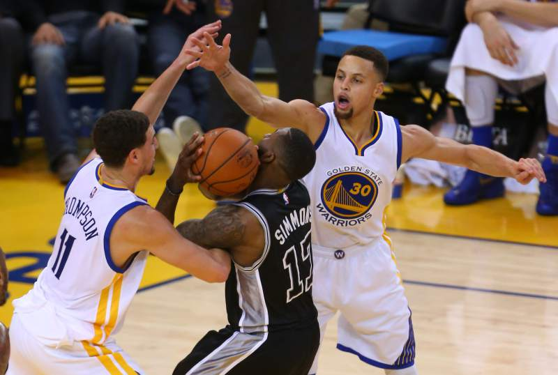 Golden State's Klay Thompson (left) and Stephen Curry collapse on San Antonio's Jonathon Simmons. Photo: Christopher Chung / The Press Democrat